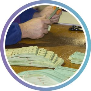 the hands of someone tallying election votes at a table