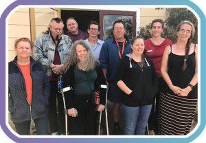nine members of Kyogle peer group pose for camera outside meeting room