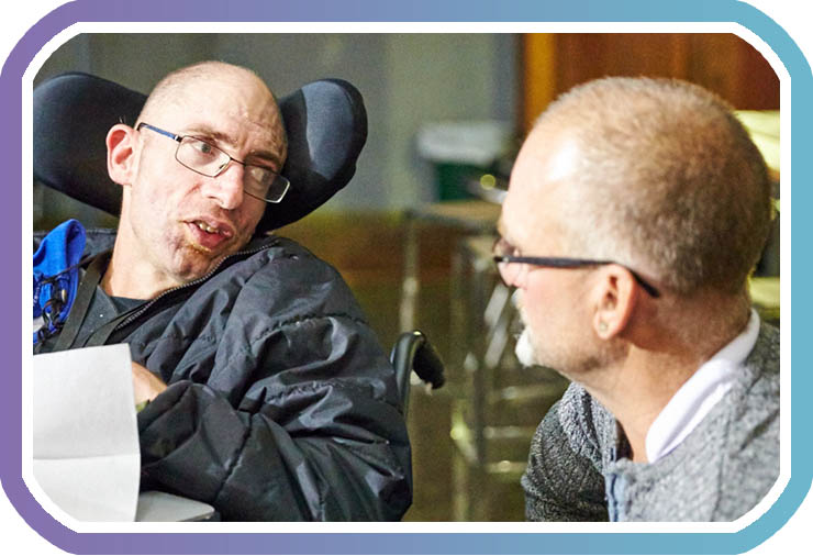 Two middle-aged men sit talking indoors, one is a wheelchair user