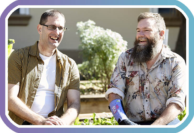 Two men sit together outside in a sunny garden area smiling at camera